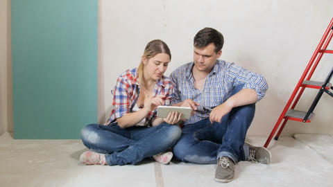 4k footage of young couple sitting on floor of their new house under renovation Footage