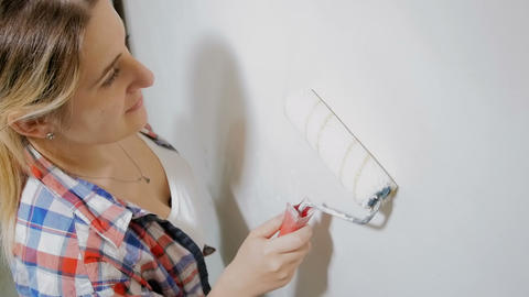 Beautiful young woman renovaating her new apartment. Young girl painting walls Live Action