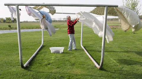 Woman hanging clothes on a clothesline Footage
