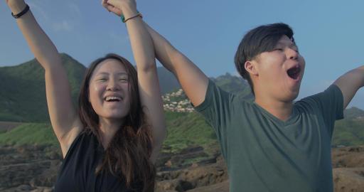 Taiwanese couple screaming to ocean mountain background beautiful location- 2 影片素材