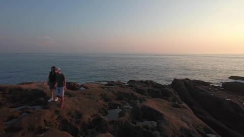 Couple walking on giant Rocks near coast line in Taiwan Aerial Shot Footage