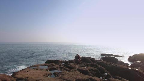 Young Couple taking selfie on beautiful Rocks Ocean side powerful waves Aerial S 影片素材