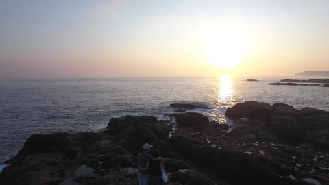 Young Taiwanese couple watching sunset on Rocks seas side powerful waves ビデオ