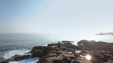 Amazing waves crashing over rocks couple walking coast Aerial Shot 影片素材