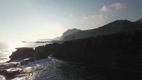 Young attractive couple waving on epic rock scene on sea coast mountain backgrou Footage