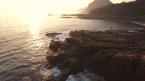 Couple standing on rocks next to sea at sunrise Aerial moving shot Shot Live Action