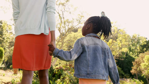 Rear view of mother and daughter are holding by hand Live Action
