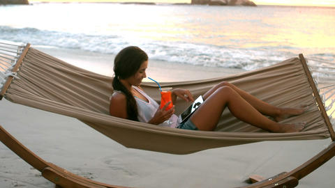 Woman using digital tablet and having mocktail on a hammock Live Action