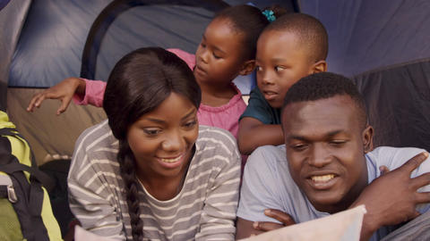 Smiling family looking at map card Live Action