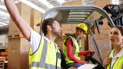 Warehouse workers interacting with forklift driver Live Action
