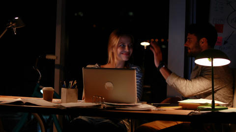 Casual colleagues using a laptop at night Live Action