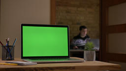 Closeup shoot of the laptop with green chroma screen lying on the desk in the Footage