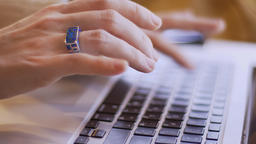 Closeup side view shoot of female hands typing on the laptop indoors in a cozy Footage