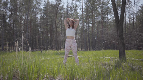 Portrait healthy graceful cute woman doing yoga fitness stretching in the forest Footage
