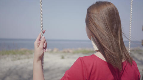 Close up portrait slim elegant woman in red dress sitting on the swing and Footage