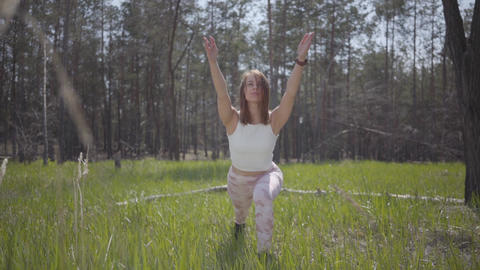 Portrait healthy peaceful cute woman doing yoga fitness stretching in the forest Footage