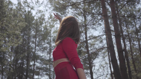 Portrait portrait graceful womans body in red dress in the forest. Lady raises Live Action