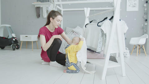Baby studying things under mom's supervision indoor Live Action