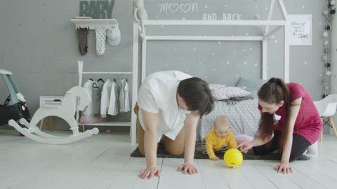 Cute baby playing ball crawling with parents at home Footage