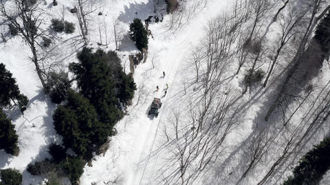 Snowboarders snowboarding tied to off road crawler car in winter countryside aerial view. People Footage