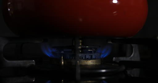 Ignition of the heat under the red pot in the kitchen Footage