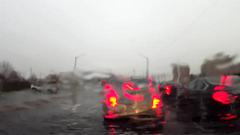 Car Waiting in Traffic While Raining on Windshield. Vehicle Idling on City Street From Driver Point Live Action