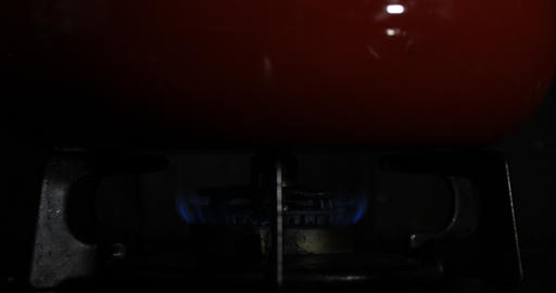 Ignition of the heat under the red pan in the kitchen Footage