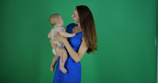 Young brunette woman touches baby's nose and he smiles, slow motion, chromakey Footage