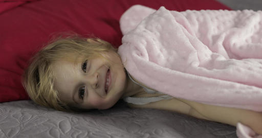 Little cheerful girl hides under a blanket on bed at home. Pretty, little girl Live Action