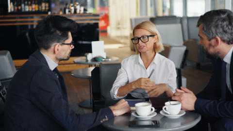 Smiling businesswoman discussing work with male partners during meeting in cafe Archivo