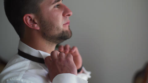 4k Wearing bow tie close up. Male hands check correct and adjust casual bow tie Live Action