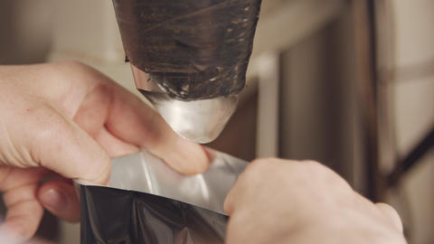 Hands of worker packing roasted coffee beans into bags Acción en vivo