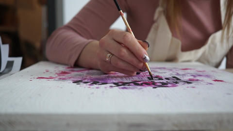 Girl artist draw abstract paintings with inscriptions. Motivational inscriptions Live Action