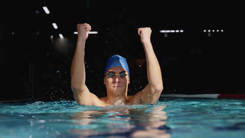 Swimmer jumping up and cheering raising arms in the pool Live Action