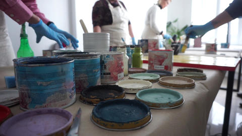 Paint cans on the table. People in aprons. Master Class. Artistic education Footage