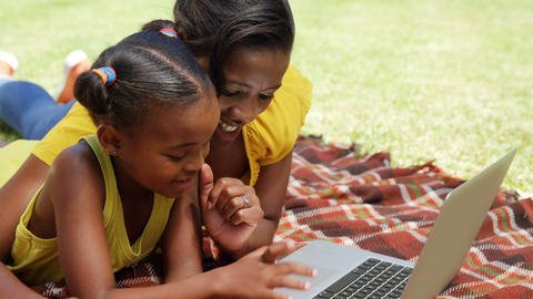 Portrait of mother and daughter are using a laptop in the garden Live Action