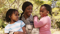 Soldier mother holding her two children in a park Footage