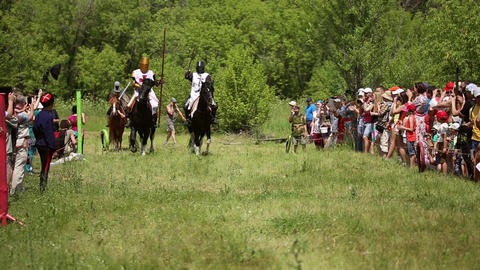 Knights in medieval clothes and helmets riding on horses Live Action
