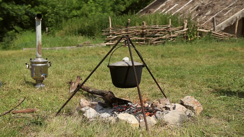 The cauldron on a tripod heated on a campfire Footage