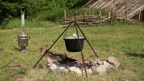 The cauldron on a tripod heated on a campfire Footage