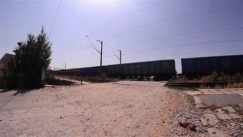 Cars passing over a railroad crossing after passing a freight train 02 Footage