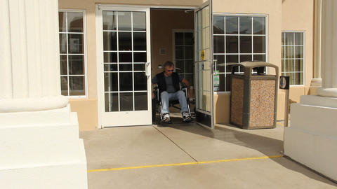 Man in a wheelchair using handicapped exit Footage