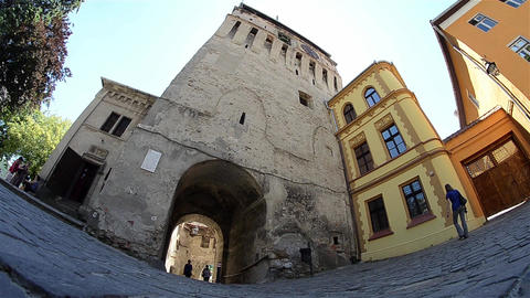 Group of tourists passing beneath an imposing tower of an old medieval gate 24 Footage