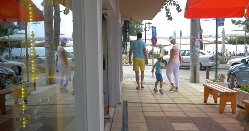 Family of three leaving store and walking in the street Footage