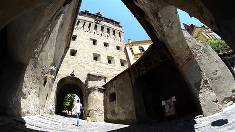 Woman walks under the ancient walls of the city and passes under the imposing ga Footage