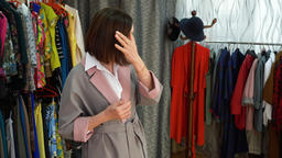 Adult woman choosing new clothes in fashion store while shopping. Seller helping Footage