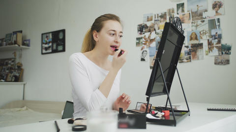 Woman applying lipstick. Young model putting on some makeup, using lipstick to Live Action