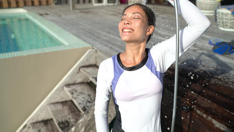 [alt video] Woman in rashguard at luxury hotel outdoor showering...