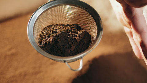 Close-up woman hands sifting cocoa powder Footage