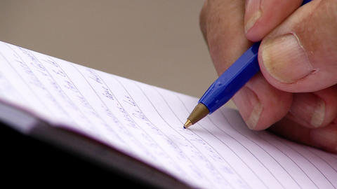 Male Hand Writing By Blue Pen Outside. Close-Up Footage